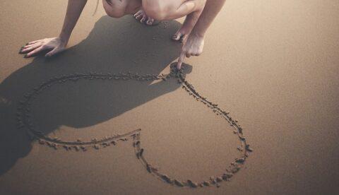 女性が砂浜に書いたハート