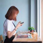 窓際で椅子に座ってスマートフォンを操作する女性