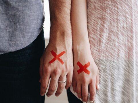手の甲に赤い×印が書かれたカップルの手