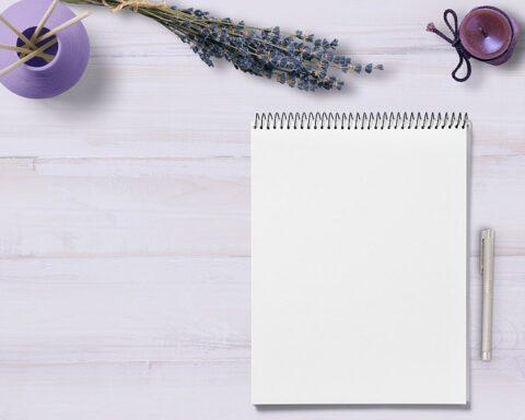 白いテーブルの上に置かれたノートとペン