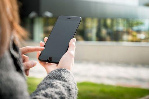 スマートフォンを右手に持って操作する女性