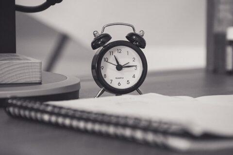 テーブルの上に置かれた時計とノート