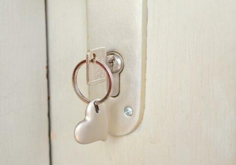 白い扉に刺さったハートのキーホルダーがついた鍵