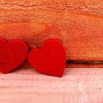 赤く色を塗った2つのハート型の木材