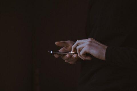 暗闇の中でスマートフォンを操作する手