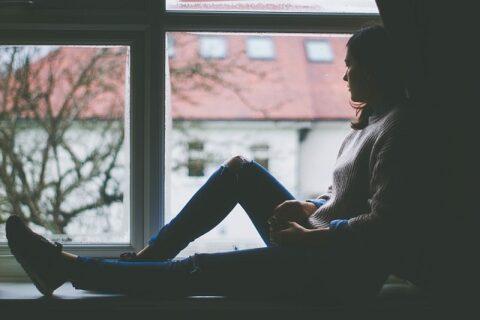 窓から外を見る女性