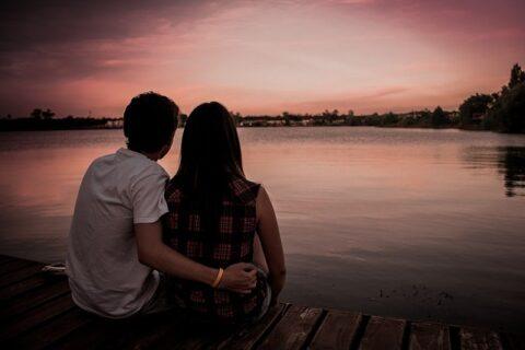 湖を眺めるカップルの後ろ姿