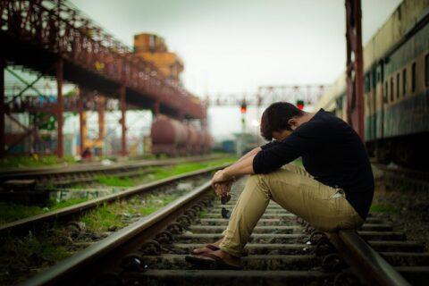 線路に座って落ち込んでいる男性