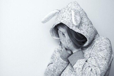 顔を手で覆って泣いている女性