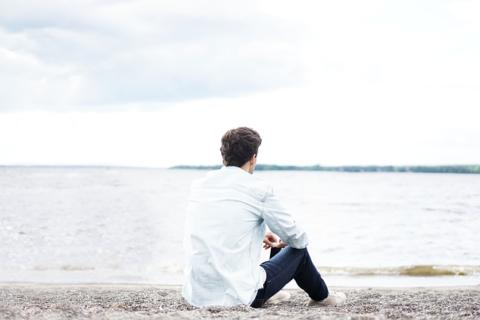 ビーチで海を眺める男性